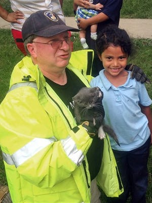 In this May 26, 2015 photo, Lancaster Township Fire Department Deputy Fire Chief  Glenn Usdin, left, holds the kitten that was rescued with the help of 6-year-old Janeysha Cruz in Lancaster, Pa. Firefighters were too big to rescue the kitten from a storm drain, so with the permission of Cruz's mother, they lowered the kindergartner nearly 3 feet into the storm drain to coax the kitten out.