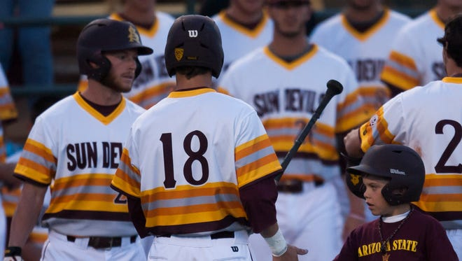 ASU's Johnny Sewald gives out handshakes returning to the dugout after safely crossing homeplate, Saturday night in Tempe, Ariz.