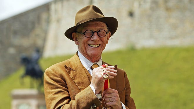British actor Sir John Hurt poses after being awarded a knighthood by Queen Elizabeth II during an Investiture ceremony at Windsor Castle on July 17, 2015 in London.