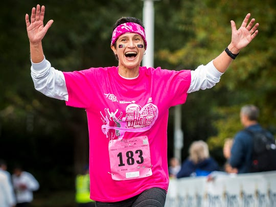 Angelina Borisov, breast cancer survivor since March 2016, celebrates as she races across the finish line for the 20th annual Susan G. Komen Knoxville Race for the Cure at World's Fair Park on Saturday, Oct. 22, 2016.