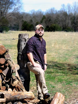 Tyler Farr stands at the fence line of his Chapel Hill, Tenn., home and farm.