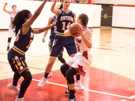 Northern's Olivia Ramsey (23) and Sarah Wight (14) guard against Port Huron's Jillian Carrier as she looks to pass the basketball during their game at Port Huron High School Dec. 8.
