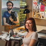 Melanie Munns poses in her painting studio in Oxford. The 29-year-old, who has been living in Oxford the past five years, is starting a project to craft portraits of ordinary people.