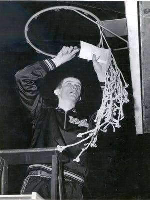 Bobby Plump of Milan High School cuts down the net after winning the 1954 state boys basketball championship at Butler Fieldhouse, Indianapolis.