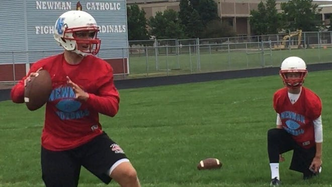 Newman Catholic quarterback Ben Bates goes through a passing drill as teammmate Dylan Ackerman looks on during a recent Cardinals practice.