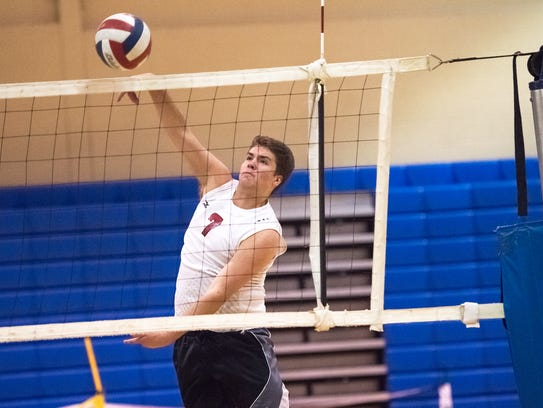 Dalton Strite spikes the ball during volleyball tryouts