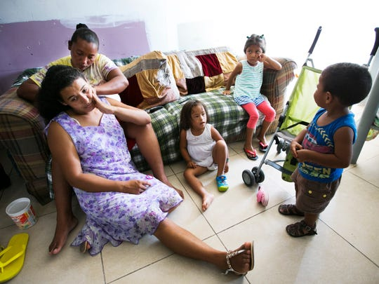 Alba Duarte, 33, (top left) of Honduras, does the hair of Carolina Galeas, 26, also of Honduras as Catalina's daughter, Joaquin Galeas, 16- months, (right) hangs out with Anni Martinez, 5, (center) also of Honduras, who has Down Syndrome, and Lydia Carrillo, 8, a Mexican migrant, at the Senda de Vida, a shelter for migrants in Reynosa, Mexico.