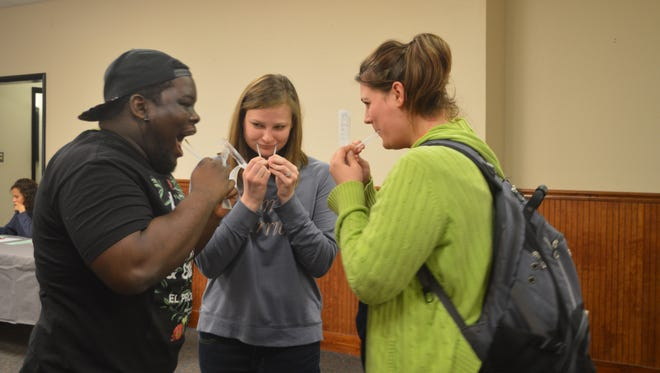 Freed-Hardeman University students swab the inside of their mouths as part of process to sign up as potential bone-marrow donors on campus on Monday.