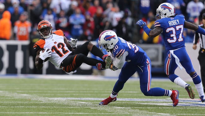 Cincinnati's Mohamed Sanu is upended by Buffalo safety Bacarri Rambo.