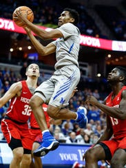 Memphis guard Jeremiah Martin (middle) drives for a