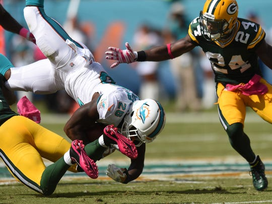 Miami Dolphins' Lamar Miller is upended by Green Bay Packers' Ha Ha Clinton-Dix as Green Bay Packers cornerback Jarrett Bush closes in on the play during the third quarter on Sunday, Oct. 12, 2014, at Sun Life Stadium in Miami Gardens, Fla. (Jim Rassol/Sun Sentinel/MCT)