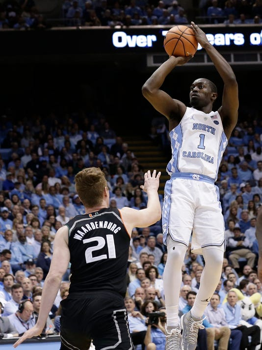 """FILE - In this Feb. 27, 2018, file photo, North Carolina's Theo Pinson (1) shoots over Miami's Sam Waardenburg (21) during the first half of an NCAA college basketball game in Chapel Hill, N.C. Making shots can be the least important skill that a """"glue guy"""" can provide. Players like Arizona's Rawle Alkins provide energy and emotion. Eric Paschall's scrappy play saves possessions for Villanova. Pinson is such a capable defender that he can take on point guards on the perimeter or bigger forwards closer to the basket. (AP Photo/Gerry Broome, File)"""