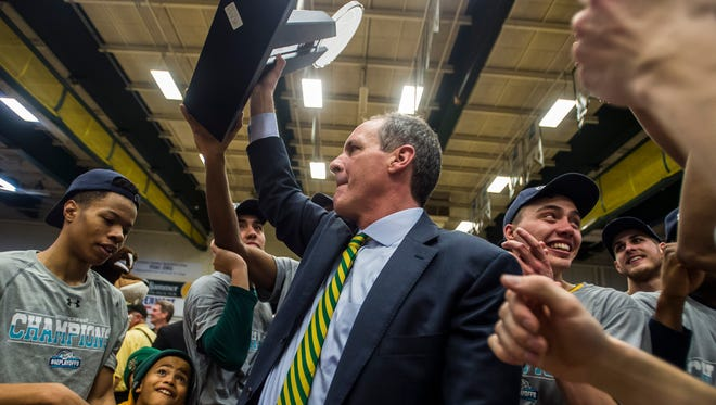 UVM Head Coach John Becker holds up the America East Championship trophy at Patrick Gym in Burlington, Vt., on Saturday, March 11, 2017, after his team won 56-53 over Albany.