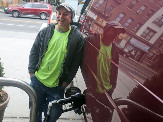 Mark Pascale, a contractor from Yonkers fills up his van at a gas station in New Rochelle, Dec. 8, 2014, where the price of regular gas was $2.85 a gallon. Pascale said that he is using the savings on gas for groceries and other regular expenses.