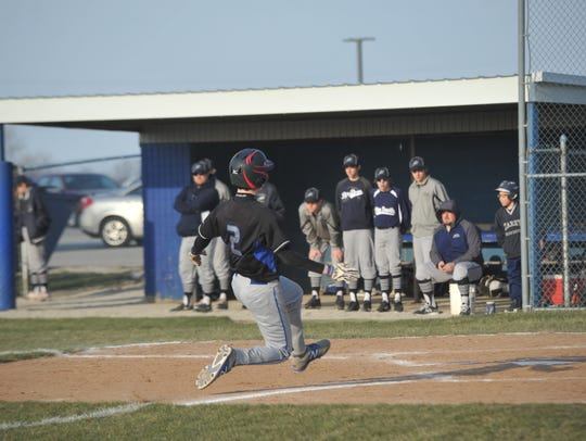 Noah Smith slides into home plate against Carey.