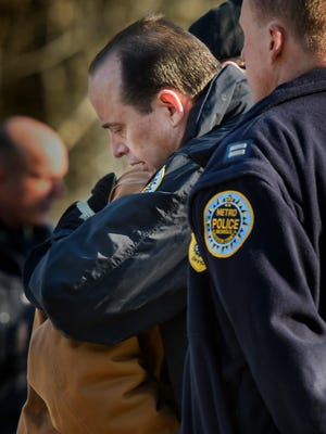 Metro Police Officer H. Hunsicker hugs a retired officer after the body of Officer Eric Mumaw was recovered Thursday, Feb. 2, 2017, in Madison.