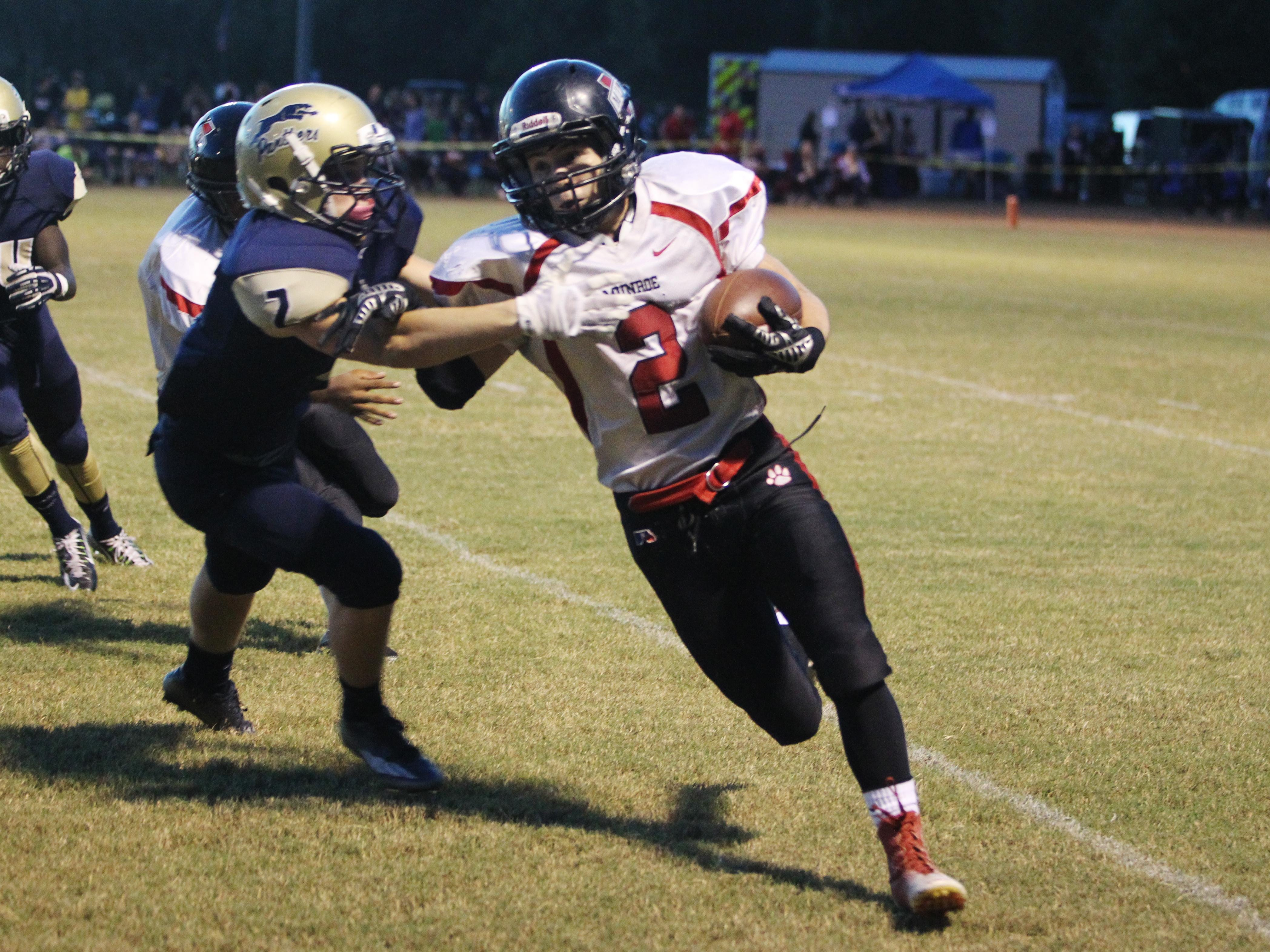 Munroe High wide receiver Hunter Ventry sprints to the outside as John Paul II safety Sam Smith closes in for the tackle.