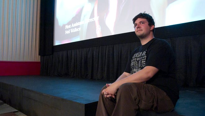 On the night of his soft grand opening, Tyler DePerro sits on the stage he had installed in one of the two theaters at Historic Howell Theater.