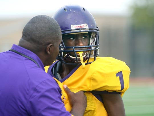 Left, East High School head coach Richard Gause talks to Kenneth Wilson during a game.