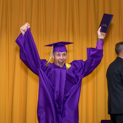 Cameron Green celebrates on stage during the graduation ceremony at Pittsville High School, Saturday, May 23, 2015.
