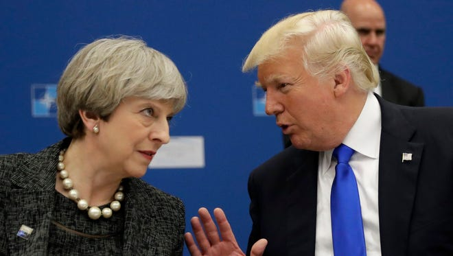 President Trump and British Prime Minister Theresa May speak during a dinner meeting at the NATO summit in Brussels, Belgium, May 25.
