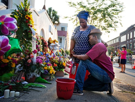 Allen Sanders, right, kneels next to his wife Georgette,