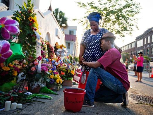 Allen Sanders, right, kneels next to his wife Georgette,