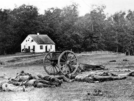 Bodies of fallen troops and a crashed gun lie on the field after the Battle of Antietam, the bloodiest one-day battle of the American Civil War, near Sharpsburg, Md., on Sept. 17, 1862.  The Dunker Church, a German Baptist Brethren, is riddled with artillery in the background.  The Battle of Antietam, led by Confederate Army Gen. Robert E. Lee, was the first major battle on Northern soil.  Casualties from both sides mounted to about 23,000.  The Confederates called it the Battle of Sharpsburg.  The Union army was under the command of Gen. George Brinton McClellan.  (AP Photo/Mathew B. Brady)