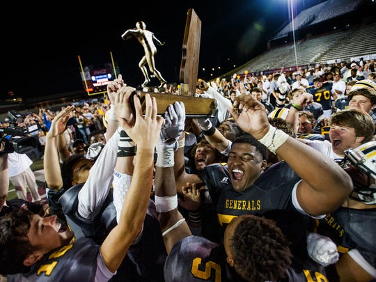 Autauga Academy players celebrate with their state championship trophy after defeating Escambia Academy during the AISA Football Tripleheader Championship at Veterans Memorial Stadium on the Troy University campus in Troy, Ala. on Friday November 18, 2016.
