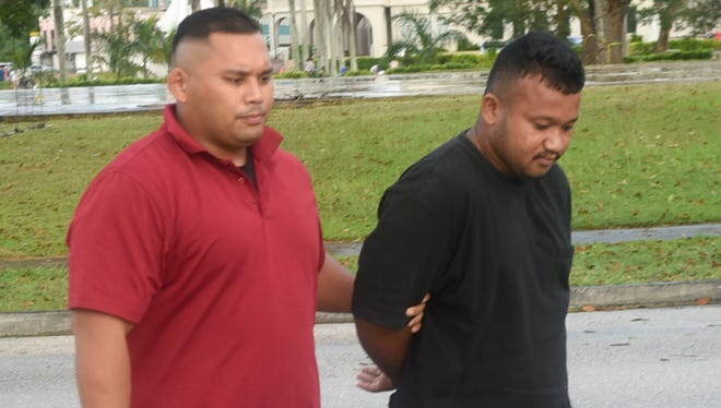 James Niosy, right, is escorted into the Guam Police Department Hagåtña precinct upon his arrest on Wednesday, Jan. 11, 2017. Niosy was arrested for allegedly falsely reporting that his 3-year-old daughter was in his car which was stolen.