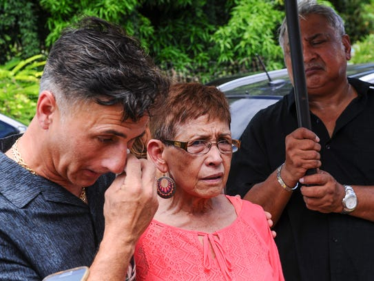 In this file photo, Walter Denton and Doris Concepcion, mother of Joseph Quinata, along with friends and supporters gather for a prayer vigil outside the administration office building of the Our Lady of Mount Carmel Catholic School in Agat.