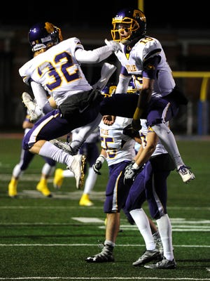 Wylie quarterback Zach Smith (19) celebrates with teammate Cason Grant (32) after a touchdown during the second quarter of the Bulldogs' 49-14 win in the Class 4A Div I state quarterfinal playoff game on Friday, Dec. 2, 2016 at San Angelo Stadium.