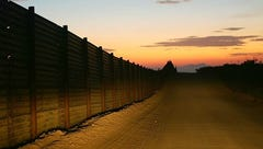 A US-Mexico border fence is illuminated by car headlights