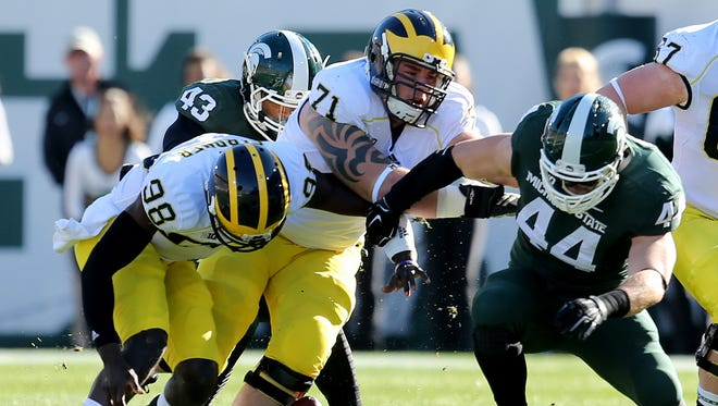 Michigan States Marcus Rush gets by Ben Braden after a fumble by Michigans Devin Gardner during first quarter action on Saturday, October 25,2014 at Spartan Stadium in East Lansing.