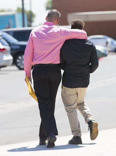 "Nick Dugas, 30, walks with his 14-year-old son, ""Bug,"" after adoption proceedings at Durango Juvenile Court in Phoenix on June 8, 2018."