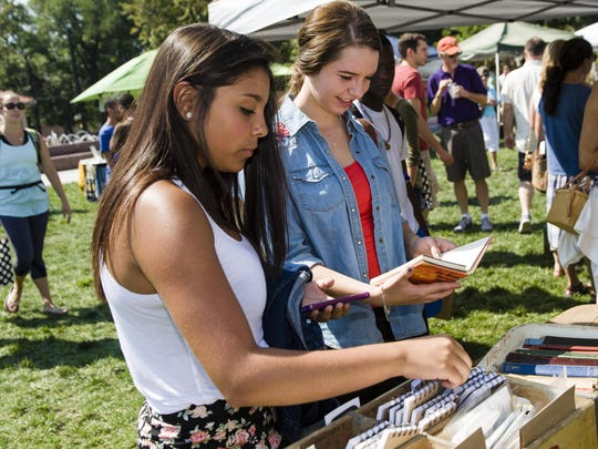 The City Flea, Cincinnati's curated urban flea market, drew shoppers to Washington Park. Paloma Clark and Megan Hughes, both of West Chester, look over the vintage journals and the old style library cards.