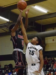 Rapides' Jerll Snowden (25, right) blocks Many's Ken Cade (4, left) as he goes for two.
