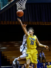 Northern Lebanon's Alex Yeager drives to the hoop and scores as he is fouled by Lebanon Catholic's Miguel Escobar as Northern Lebanon defeated Lebanon Catholic 52-49 on Monday, December 14, 2015.