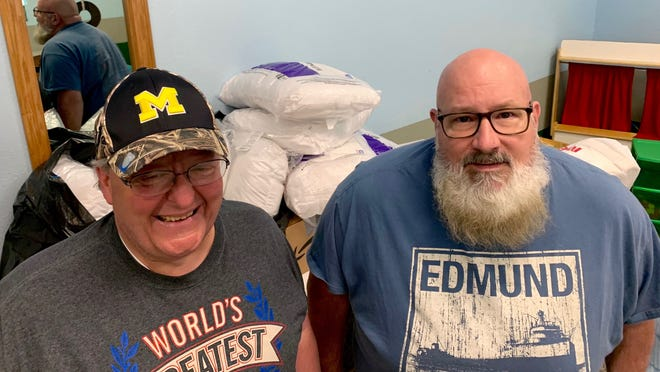 Doug Corona and Bob Finegan work on organizing donations at Hillsdale City Church for flooded victims in Midland and Sanford.