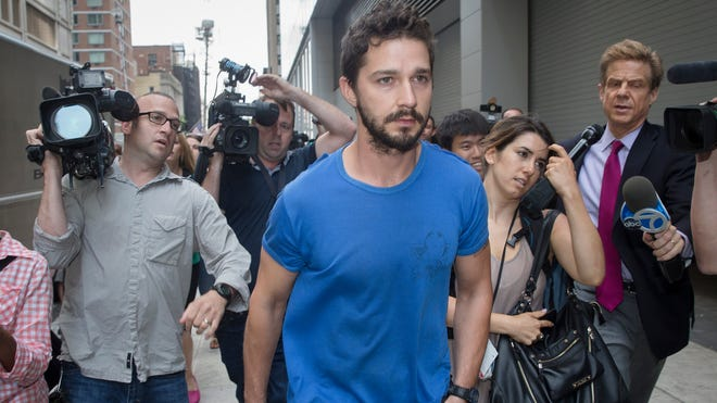 """Shia LaBeouf walks through the media after leaving Midtown Community Court following his arrest the previous day for yelling obscenities at the Broadway show """"Cabaret,"""" Friday, June 27, 2014, in New York."""