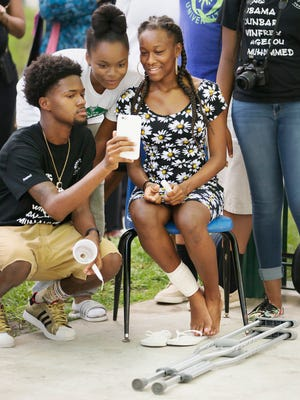 Alanna Campbell, 14, right, attends a community vigil Thursday at the Quality Life Center in Fort Myers. Campbell was shot in the leg Monday while at a teen party at the Club Blu nightclub in Fort Myers. The vigil honored those killed and injured in the shooting.