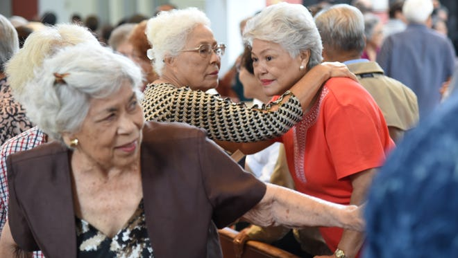 In this Dec. 8, 2016, file photo, parishoners offer gestures of peace during a Mass in honor of Guam's World War II survivors at the Dulce Nombre de Maria Cathedral-Basilica in Hagåtña.