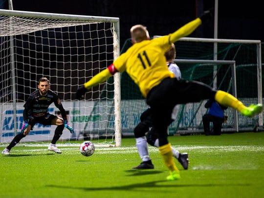FC Haka goalkeeper Mike Hartmann collects a rolling shot.