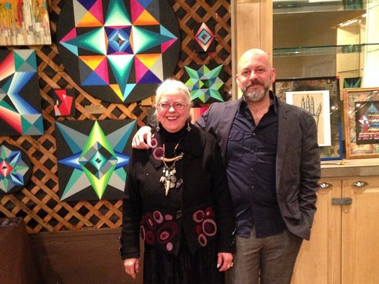 Cher Shaffer with her son, Gabriel Shaffer, in front of an exhibition of Gabriel's pieces, which were inspired by his grandmothers' quilting patterns.