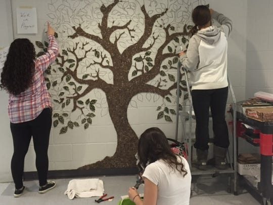 Old Bridge High School art students painstakingly create a giving tree to recognize efforts of students and staff. Left to right standing are Christina Tedeschi and Georgia Brennan; seated is Michelle Schmitz. All are seniors.