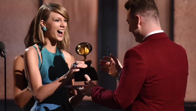Taylor Swift, left, presents Sam Smith with the award for best new artist at the 57th annual Grammy Awards on Sunday, Feb. 8, 2015, in Los Angeles.