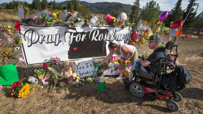 Candida Miller, left, and Brandon Snyder leave flowers at a site of a growing memorial to victims of the mass shooting at Umpqua Community College in Roseburg, Ore., on Tuesday.