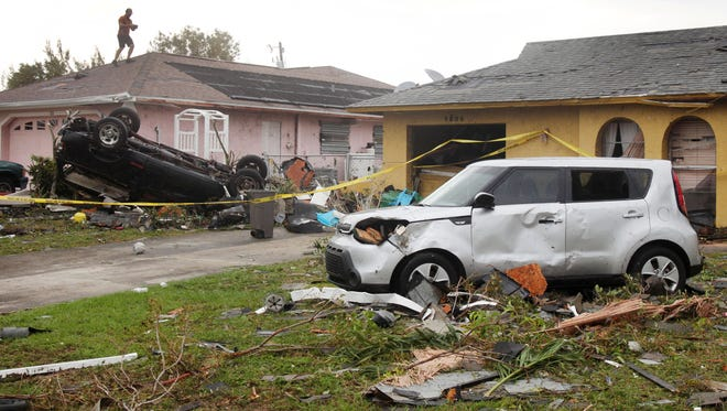 Cape Coral residents assess the damage to homes on Southwest 15th Avenue on Sunday morning.
