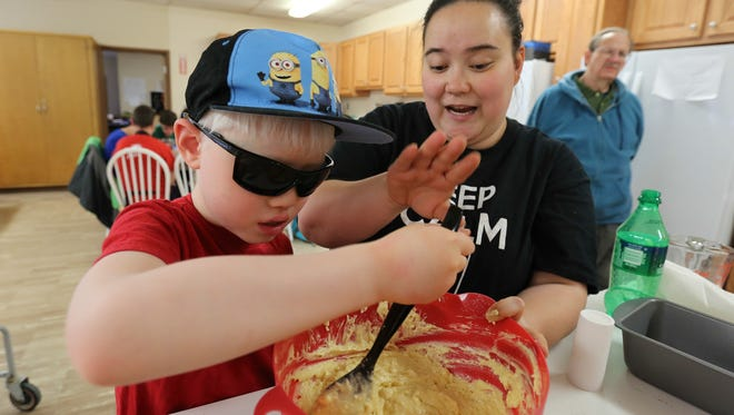 Mikah Taylor, with a little assistance from Tara Harmon, mashes up potatoes as he helps to prepare shepherd's pie at the Kentucky School for the Blind.March 167, 2017