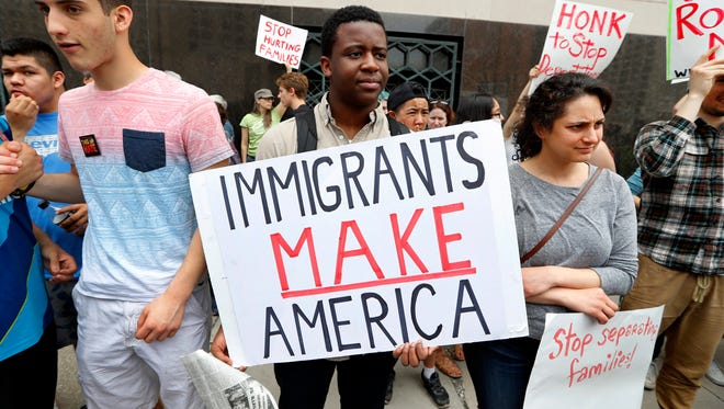 In this Tuesday, May 16, 2017, file photo, Torianto Johnson, a freshman at Pioneer High School in Ann Arbor, holds a sign supporting immigrants during a rally outside a federal courthouse in Detroit. Protesters rallied in hopes public outcry will again delay the deportation of Jose Luis Sanchez-Ronquillo from the United States to Mexico. U.S. immigration arrests increased nearly 40 percent in early 2017 as newly emboldened agents under President Donald Trump detained more than 40,000 people suspected of being in the country illegally, with a renewed focus on immigrants without criminal convictions.